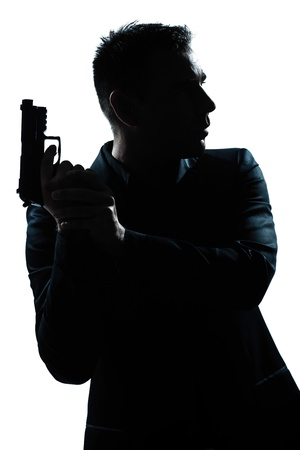 man holding gun: one caucasian spy criminal policeman detective man holding gun portrait silhouette in studio isolated white background Stock Photo