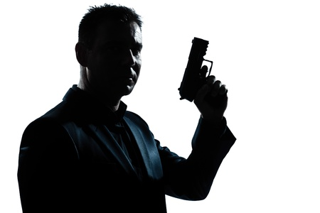 one caucasian spy criminal policeman detective man holding gun portrait silhouette in studio isolated white background photo