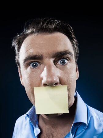 caucasian man surprised mouth shut by note paper portrait isolated studio on black background photo