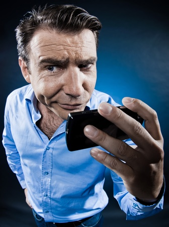 hesitancy: caucasian man portrait cellphone doubtful isolated studio on black background
