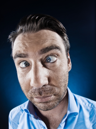 squinting: caucasian man unshaven squinting eye problem portrait isolated studio on black background Stock Photo