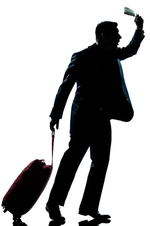 one caucasian business traveler man walking with suitcase hurrying late  full length silhouette in studio isolated white background photo