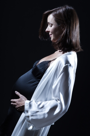 side profile: beautiful smiling caucasian pregnant  woman portraitt   touching her belly in nightie on studio isolated black background