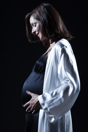 beautiful smiling caucasian pregnant  woman portraitt   touching her belly in nightie on studio isolated black background Stock Photo - 13888640