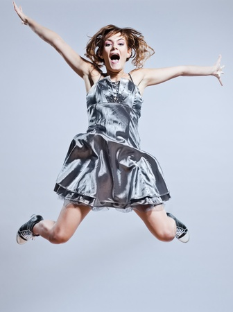 beautiful young caucasian woman girl evening dress jumping screaming happy on studio isolated plain background photo