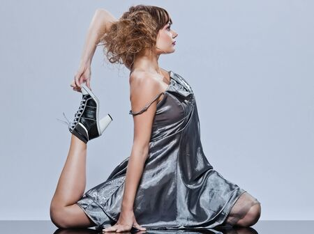 supple: beautiful young caucasian woman girl evening dress supple stretching on studio isolated plain background