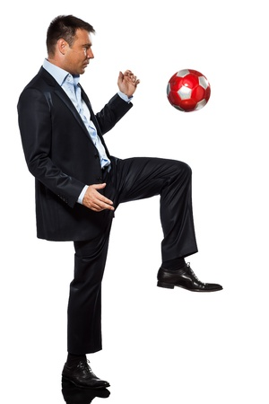 juggling: one caucasian business man playing juggling soccer ball in studio isolated on white background