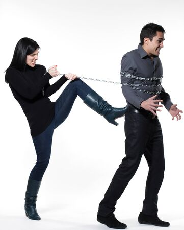 arrogant: woman binding his man with a chain on white background