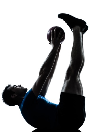 lying on the stomach: one caucasian man exercising workout holding fitness ball posture in silhouette studio  isolated on white background