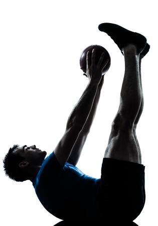 un hombre caucásico ejercicio de entrenamiento de la aptitud celebración postura de pelota en el estudio de la silueta sobre fondo blanco