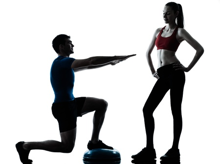 personal trainer man coach and woman exercising squats on bosu silhouette  studio isolated on white background photo