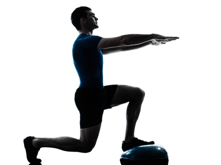 crouches: one caucasian man exercising bosu workout fitness in silhouette studio  isolated on white background Stock Photo