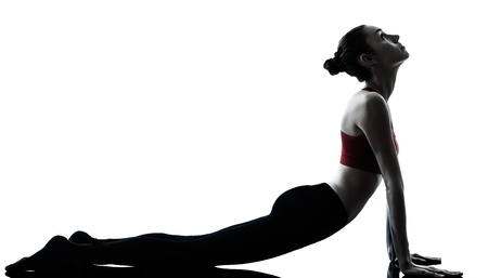 one caucasian woman sun salutation yoga surya namaskar posture position in silhouette in studio isolated on white background full length photo