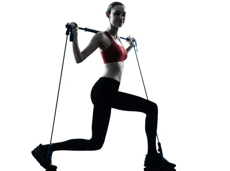 one caucasian woman exercising elastic gymstick in silhouette studio isolated on white background photo
