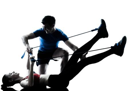 パーソナル トレーナーの男性コーチと行使 gymstick シルエット スタジオ白い背景で隔離の女性 写真素材