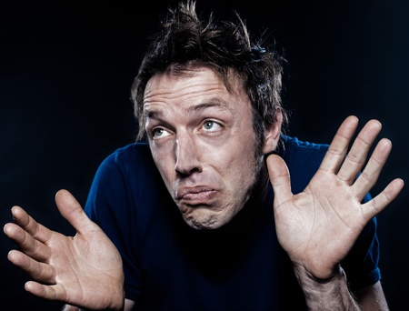 hesitancy: studio portrait on black background of a funny expressive caucasian man frowning ignorant