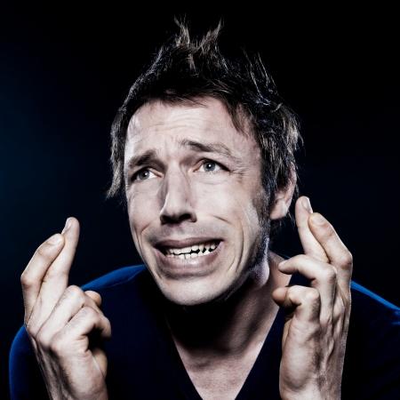 Studio Portrait auf schwarzem Hintergrund eines lustigen ausdrucksvollen kaukasisch Mann mit gekreuzten Fingern in der Hoffnung Glück