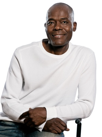 1 mature man: Portrait of a casual handsome afro American man smiling while sitting in studio on white isolated background Stock Photo