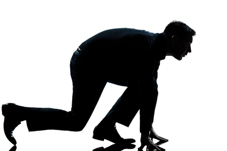cut the competition: one caucasian man in starting block posture ready to run full length silhouette in studio isolated white background Stock Photo