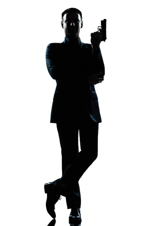 one caucasian secret agent in a james bond posture holding gun full length silhouette in studio isolated white background photo