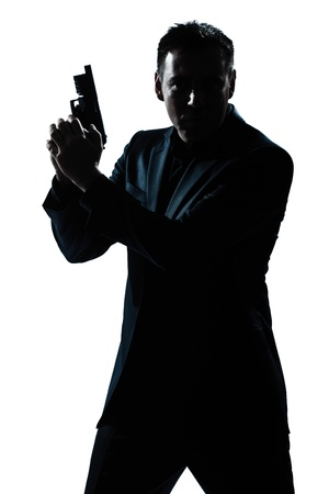 one caucasian spy criminal policeman detective man holding gun portrait silhouette in studio isolated white background photo