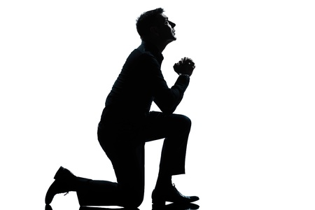 man side view: one caucasian man kneeling praying  full length silhouette in studio isolated white background