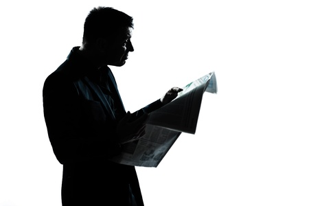 eading: one caucasian man portrait silhouette eading newspaper in studio isolated on white background