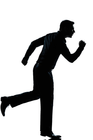 one caucasian business  man running full length silhouette in studio isolated white background photo