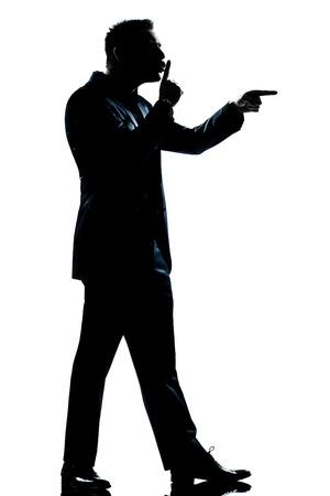 threatening: one caucasian man menace hushing for silence full length silhouette in studio isolated white background