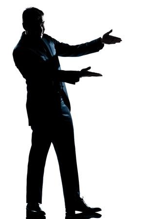 un hombre caucásico que muestra la silueta vacía apuntando espacio de la copia de longitud completa en el estudio de fondo blanco aislado Foto de archivo