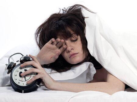 an awakening: young woman woman in bed awakening tired holding alarm clock on white background