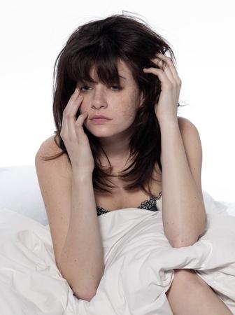 giovane donna in hangover risveglio insonnia letto stanco in un lenzuolo bianco su sfondo bianco Archivio Fotografico