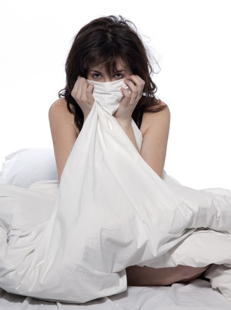 sulk: one young woman in bed awakening tired insomnia hangover  in a white sheet bed on white background Stock Photo