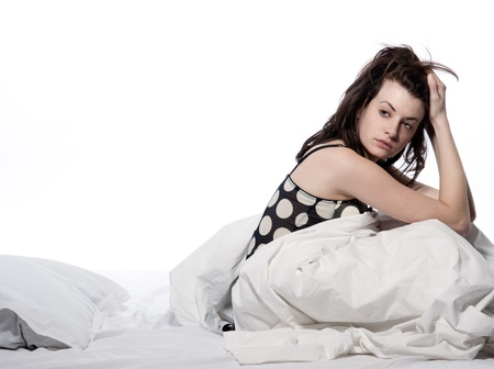 bad hair: one young woman in bed awakening tired insomnia hangover  in a white sheet bed on white background Stock Photo