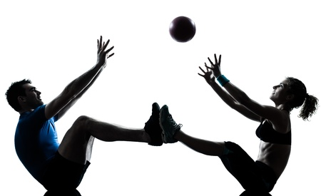 fitness ball: one caucasian couple man woman personal trainer coach exercising tossing fitness ball silhouette studio isolated on white background Stock Photo