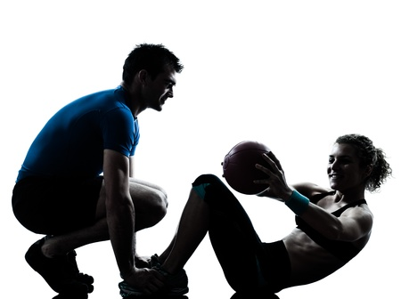 one caucasian couple man woman personal trainer coach exercising weights fitness ball silhouette studio isolated on white background photo