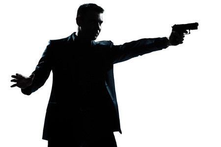 one caucasian man with gun aiming portrait silhouette in studio isolated white background photo