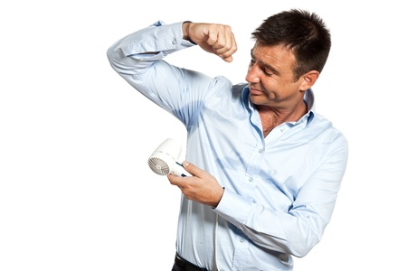 perspiring: one caucasian man with sweat stain perspire drying shirt with hair dryer in studio isolated on white background Stock Photo