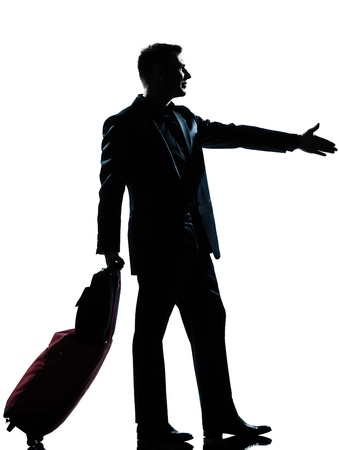 business traveler: one caucasian man one caucasian business traveler man handshake  with suitcase  full length silhouette in studio isolated on white background Stock Photo