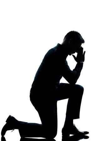 een blanke man knielt volle lengte silhouet in de studio geïsoleerde witte achtergrond