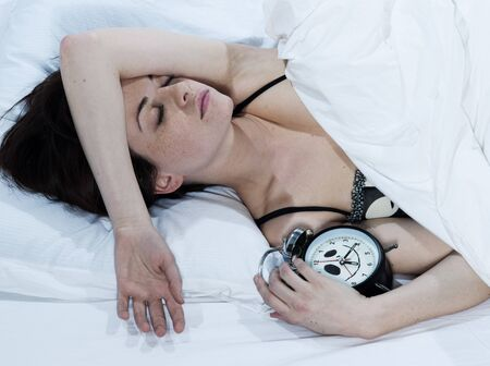 young woman in a white sheet bed on white background sleeping with her alarm clock Stock Photo - 14381517