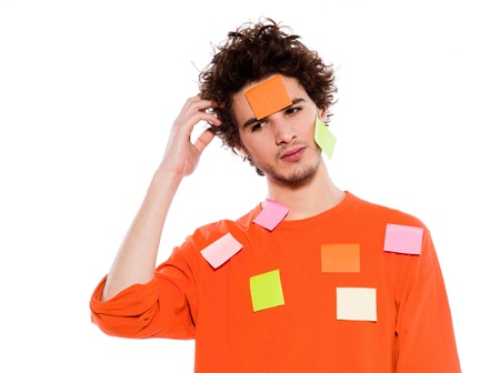 one young thinking with adhesive notes covering caucasian man portrait in studio on isolated white background photo