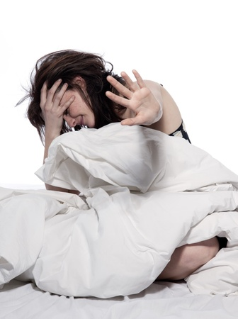 timidity: one young woman in bed awakening tired insomnia hangover  in a white sheet bed on white background Stock Photo