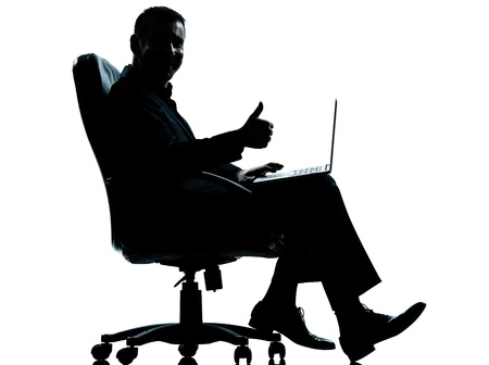a l ecart: one caucasian business man computer computing thumb up sitting in armchair silhouette Full length in studio isolated on white background Stock Photo