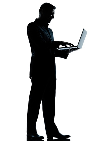 ombres: one caucasian business man computing computer laptop silhouette standing Full length in studio isolated on white background