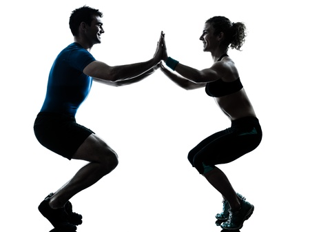 a l ecart: one caucasian couple man woman personal trainer coach exercising squatts silhouette studio isolated on white background Stock Photo