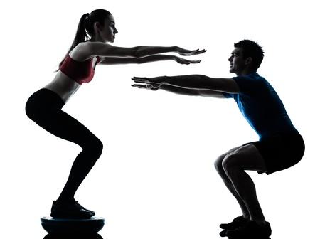 hommes: el entrenador personal del hombre y la mujer el ejercicio de entrenador se pone en cuclillas en el estudio de la silueta bosu aisladas sobre fondo blanco Foto de archivo