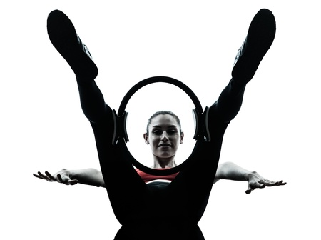 a l ecart: one caucasian woman exercising pilates ring in silhouette studio isolated on white background