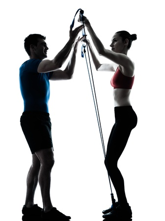 a l ecart: personal trainer man coach and woman exercising gymstick silhouette  studio isolated on white background