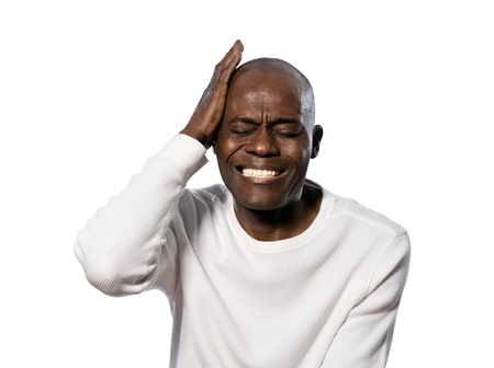 Close-up of an afro American man with a severe headache in studio on white isolated background Stock Photo - 14401763